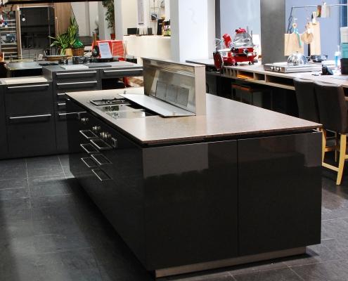 kücheninsel mit ausgefahrenem phönix dunstabzug und offener fettfilterabdeckung