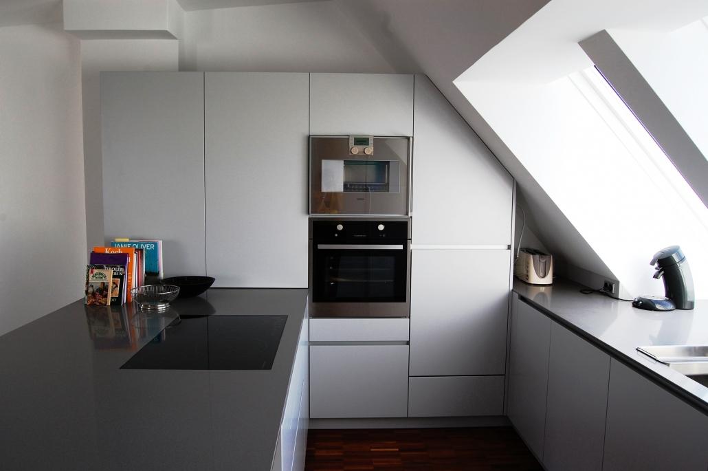 weiße grifflose küche mit dunkelgrauer arbeitsfläche