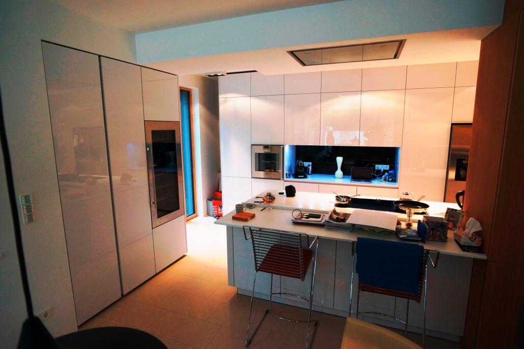 weiße grifflose küche mit kochinsel und gaggenau geräten